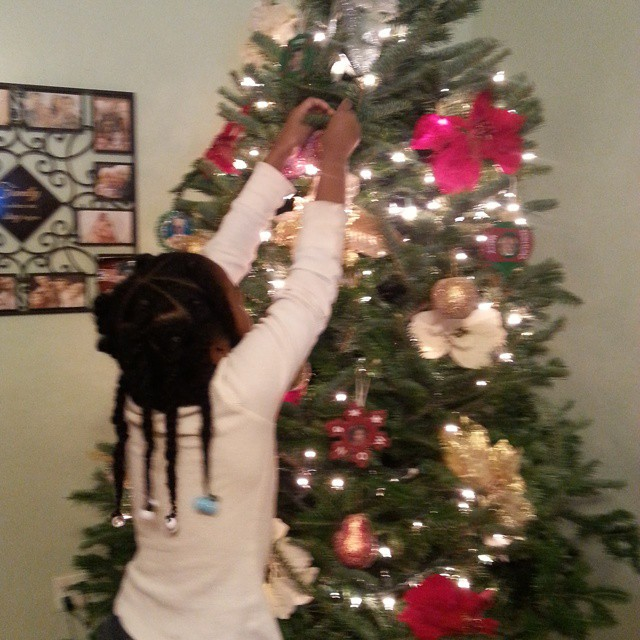 My little elf is helping to decorate the Christmas tree.