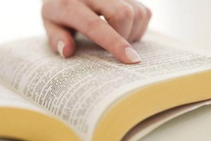 Woman's finger on page in Bible